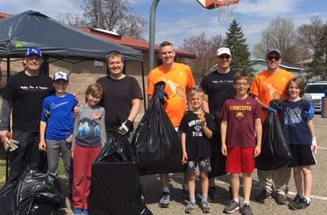 Group poses with litter collected during Earth Day Cleanup